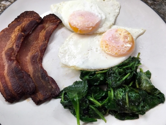 Over easy eggs, bacon, and sauteed spinach with a splash of balsamic vinegar.